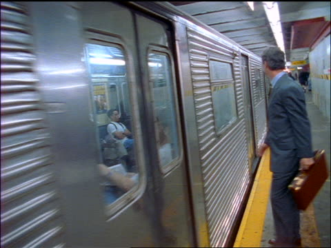dolly shot upset businessman trying to enter subway train as it pulls away from station / checks watch / nyc - one mid adult man only stock videos & royalty-free footage