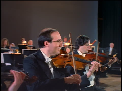 dolly shot violinists playing in orchestra - バイオリン奏者点の映像素材/bロール