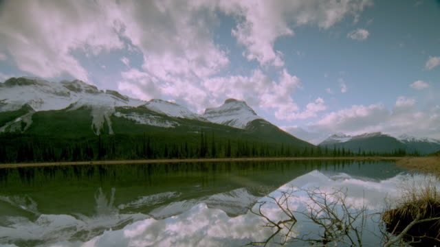 vídeos y material grabado en eventos de stock de dolly shot wide shot time lapse white clouds moving over snowcapped rocky mountains / reflected in water in foreground / canada - parque nacional de jasper