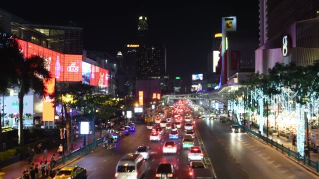Dolly shot wide time lapse night of traffic and famous mall in business district Bangkok,Thailand