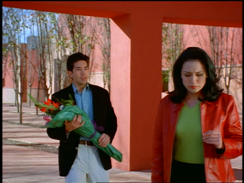 dolly shot with slow zoom in man with flowers runs to upset woman + pleads with her / in covered walkway with columns