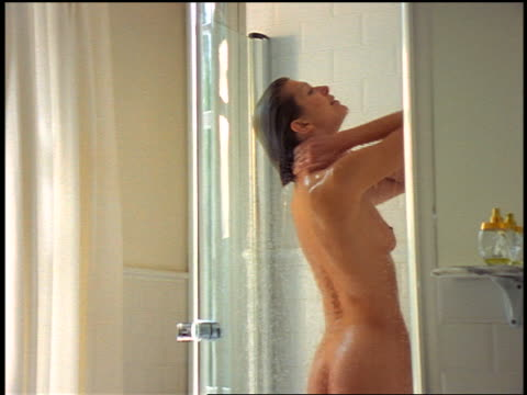 dolly shot woman bathing in glass-doored shower