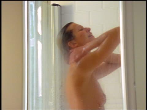 vidéos et rushes de dolly shot woman bathing in glass-doored shower - cheveux mouillés