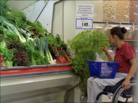 dolly shot woman in wheelchair picking out produce in supermarket + putting into basket - lettuce stock videos and b-roll footage