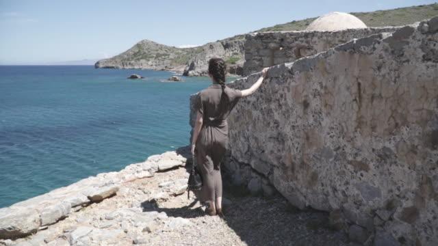 Dolly shot, woman looking at view of Mediterranean Sea