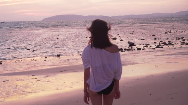 Dolly shot, woman looks out at ocean in Thailand
