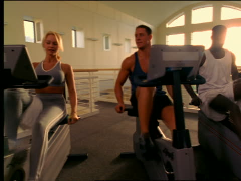 dolly shot woman, man + black man riding exercise bikes in health club - femmina con gruppo di maschi video stock e b–roll