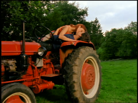 dolly shot woman + man kissing on tractor in wilderness / signaling for camera to go away