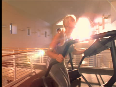 vídeos de stock, filmes e b-roll de dolly shot woman on stairmaster + man on treadmill in health club - aparelho de musculação