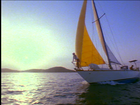 vidéos et rushes de dolly shot pan woman sitting on bow of sailboat sailing quickly / people in back of boat / virgin gorda - angle de prise de vue