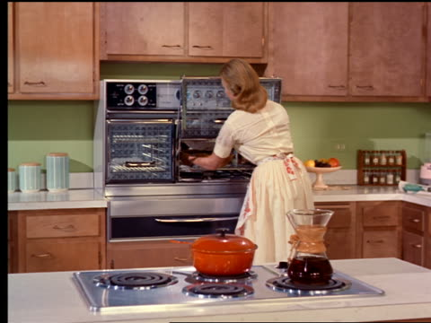 1962 dolly shot woman taking dish out of oven in kitchen + putting parsley on it - hausfrau stock-videos und b-roll-filmmaterial