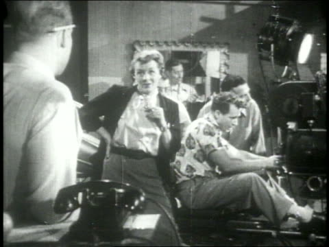 B/W 1951 dolly shot woman talking to man who picks up phone in movie studio