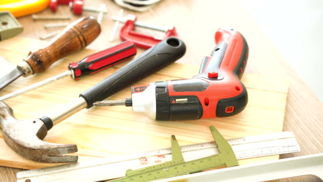 dolly shot: work tool of wooden craftman such as hammer, protective glove, level, cordless screwdriver drill and knife - vernier calliper stock videos & royalty-free footage