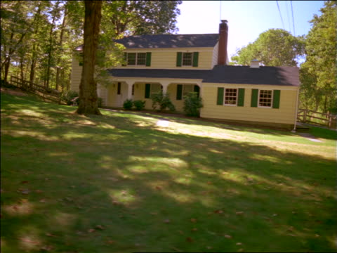 vidéos et rushes de dolly shot yellow painted 2-story house on lawn by trees - propriétaire immobilier