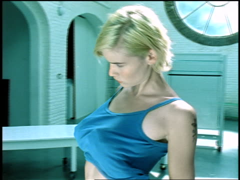 dolly shot young blonde woman standing in front of mirror feeling her breasts under blue tank top