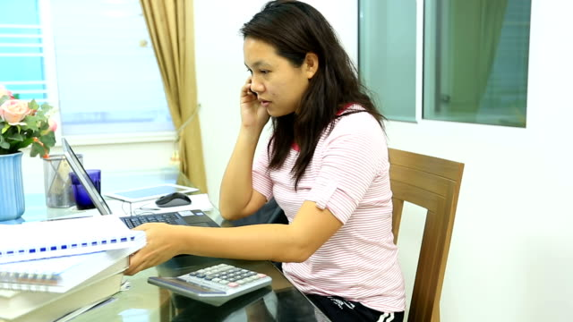 Dolly shot: Young female adult using laptop and phone working