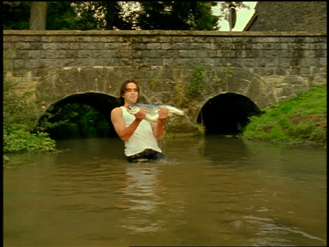 dolly shot young man standing in river by bridge pulling fish from water + smiling at camera