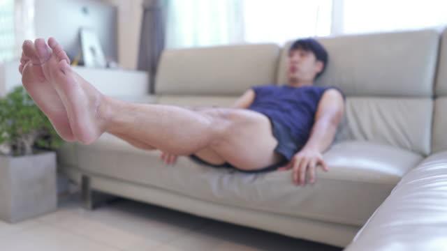 dolly erschoss den jungen mann mit sofa als unterstützung beim training des bauchmuskels. - trainingsraum wohnraum stock-videos und b-roll-filmmaterial
