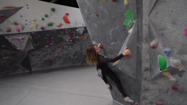 ws dolly shot young woman climbing a climbing wall - climbing wall stock videos & royalty-free footage