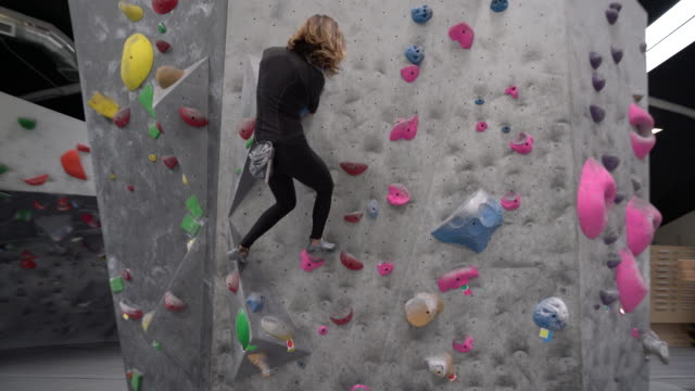 ws dolly shot young woman climbing up a wall - rock climbing stock videos and b-roll footage