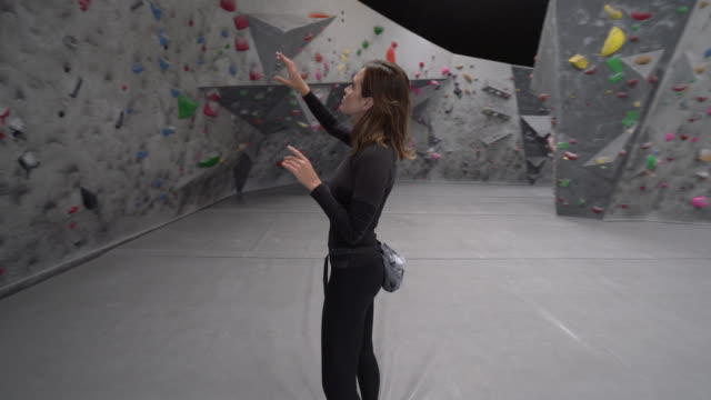 WS Dolly Shot, Young Woman looking at a climbing wall