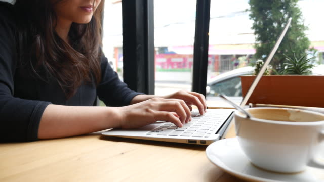 Dolly shot Young woman typing at laptop in Cafe