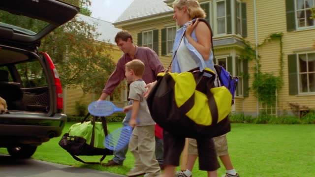 dolly shot zoom in family walking with luggage across yard to car / girl + dog getting out of car trunk