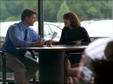 dolly shot zoom in salesman fillout out forms with woman in car dealership - showroom stock videos and b-roll footage