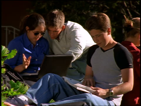 vídeos y material grabado en eventos de stock de dolly shot zoom out group of teens sitting in grass studying / boy + asian girl use laptop / others read books - libro de texto
