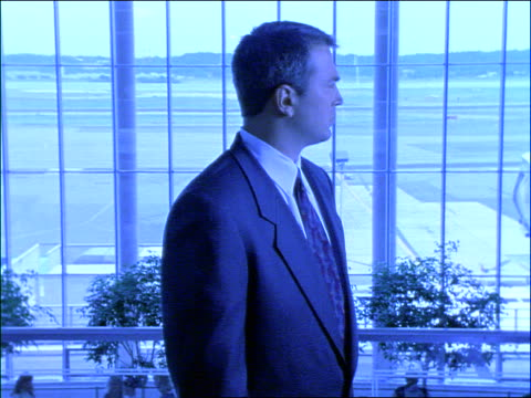blue dolly shot, zoom out to businessman turning to camera + looking sad or annoyed in airport, shakes head - nur männer über 30 stock-videos und b-roll-filmmaterial