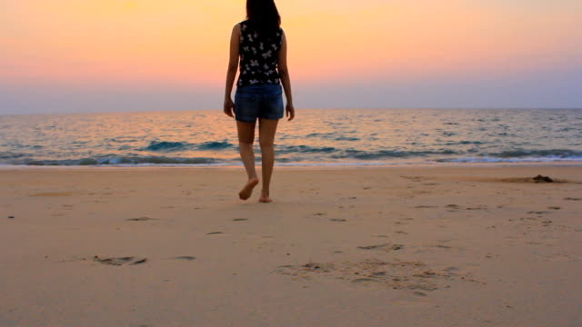 dolly shot:asian woman walking on the sunset beach - leaving stock videos & royalty-free footage