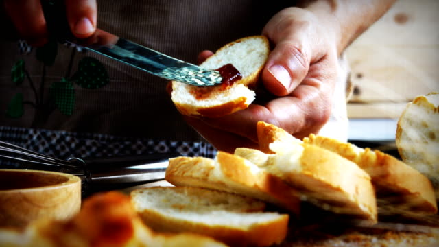 Dolly shot:Close-up of a young man's hands Bread with Jam strawberry.