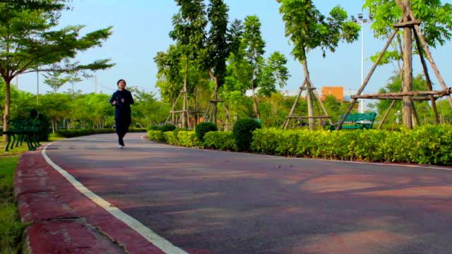 stockvideo's en b-roll-footage met dolly shot:girl jogging in park - jogster