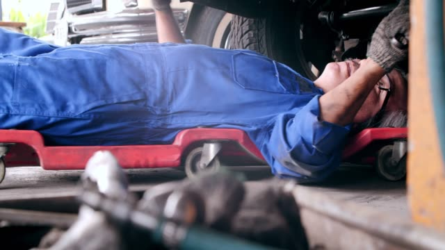 stockvideo's en b-roll-footage met dolly shot, mechanic senior man aan het werk op workshop auto service, reparatie, onderhoud en mensen concept. - monteur