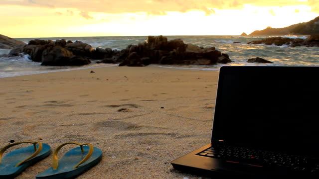 Kamerafahrt mit Dolly: Notebook und Sandalen am Strand
