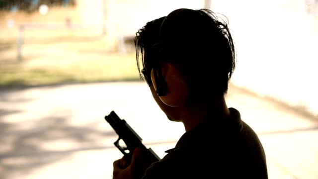 2 dolly shots of man in silhouette loading a handgun with ammo clip before shooting - arma da fuoco video stock e b–roll