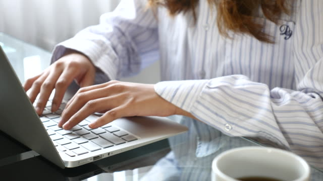 Dolly shot:Young woman working on the laptop with coffee cup