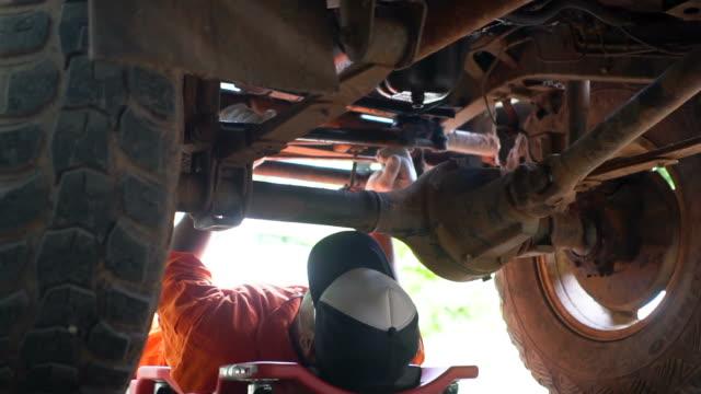 vidéos et rushes de côté de chariot de travail mecanicien voiture mâle sous le moteur du véhicule - mécanicien