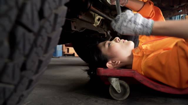 dolly side view: Asian young female car mechanic Working under vehicle engine
