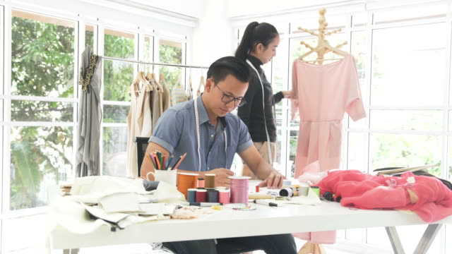 vídeos de stock e filmes b-roll de dolly side view: male and female fashion designer design and write together in home office - 30 34 years