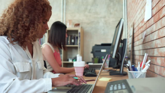dolly side view of corporate modern office with rows asian beautiful businesswomen working on desktop computer and laptop with a european woman colleague. - white collar worker stock videos & royalty-free footage