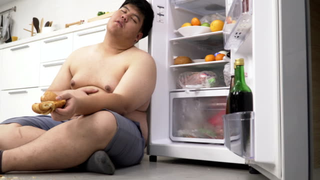 dolly side view: overweight Thai man eating until he sleeping at refrigerator