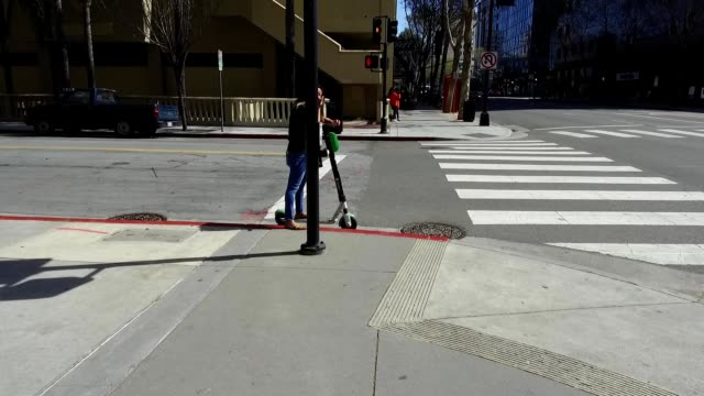 Dolly style stabilized camera shot traveling down street in the Silicon Valley town of San Jose California and panning across person riding Lime...