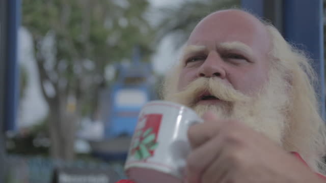 c/u dolly track side, big man w/ white long hair (santa claus), beard and moustache drinking in a cup in a terrace - beard stock videos & royalty-free footage