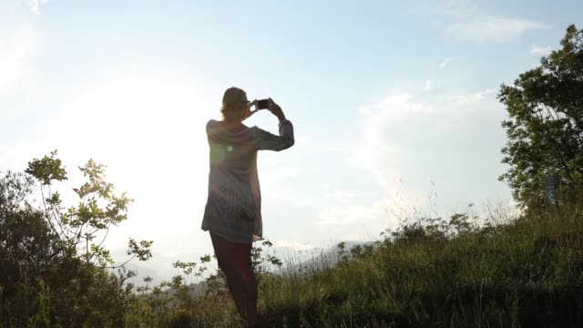 dolly tracking view of woman walking into mountain meadow - 55 59 anni video stock e b–roll
