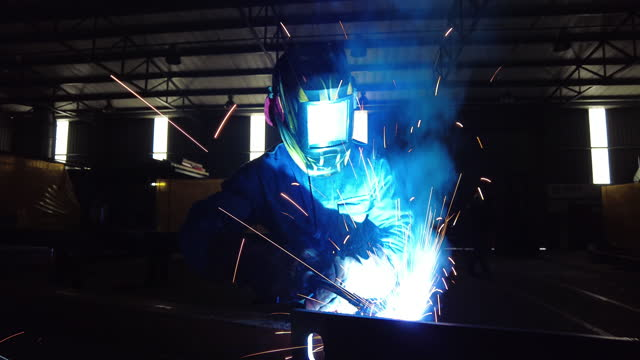 dolly upwards person welding in protective gear and helmet in the dark - welding helmet stock videos & royalty-free footage