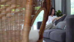 4K Dolly wide shot of Beautiful young asian woman relax sitting on sofa in home living room and reading fiction book. Pretty teenage girl resting on sofa and enjoying to read at home in weekend alone.
