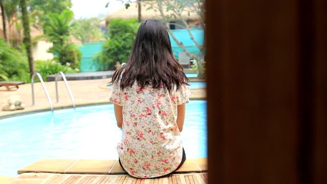 dolly hd: donna seduta sul bordo della piscina. - piscina pubblica all'aperto video stock e b–roll