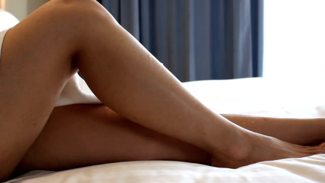 dolly women leg on the bed relax time - massage oil videos stock videos and b-roll footage