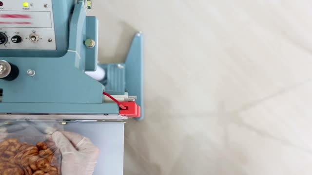 dolly: worker using thermal sealer to seal food package - packaging stock videos & royalty-free footage
